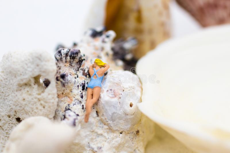 Миниатюрные люди: путешественник загорая на раковинах на пляже Польза изображения для концепции деловых поездок стоковые изображения