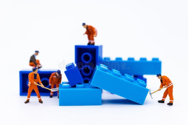 Миниатюрные люди: Работники ремонтировать, аранжируя компоненты для строительства Изображения пользы для строительного бизнеса стоковые фото