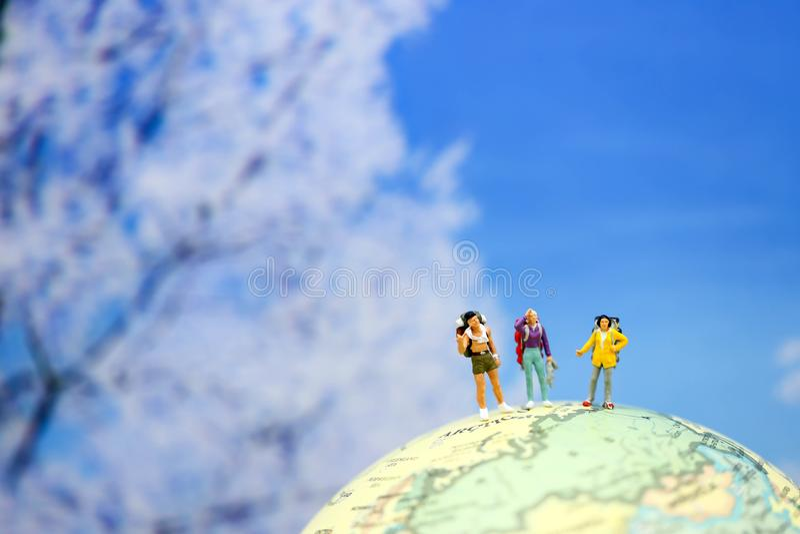 Миниатюрные люди: Рюкзак путешественника стоя на worldmap sn стоковые изображения