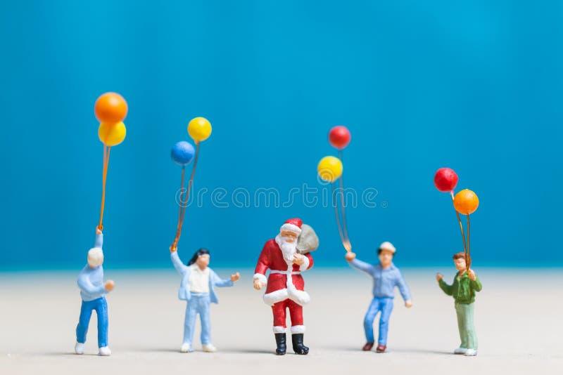 Миниатюрные люди: Санта Клаус и дети держа воздушный шар стоковое изображение rf