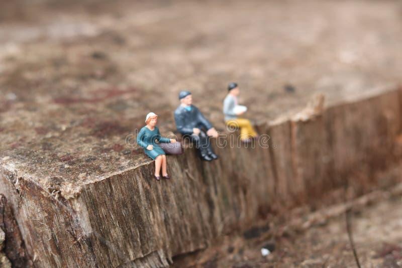 Миниатюрные люди сидя вниз на уступе стоковая фотография rf