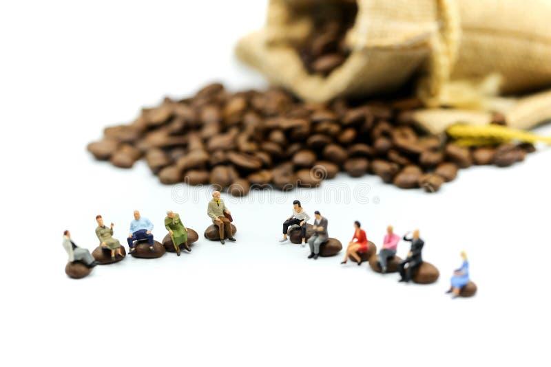 Миниатюрные люди: люди сидя на кофейных зернах Roasted используя стоковая фотография