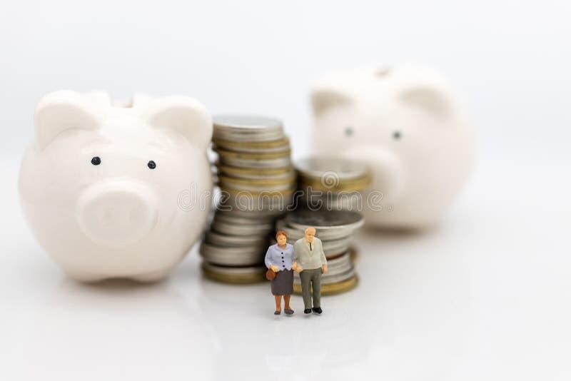 Миниатюрные люди, старые пары вычисляют сидеть na górze монеток стога используя как планирование выхода на пенсию предпосылки, ко стоковая фотография rf