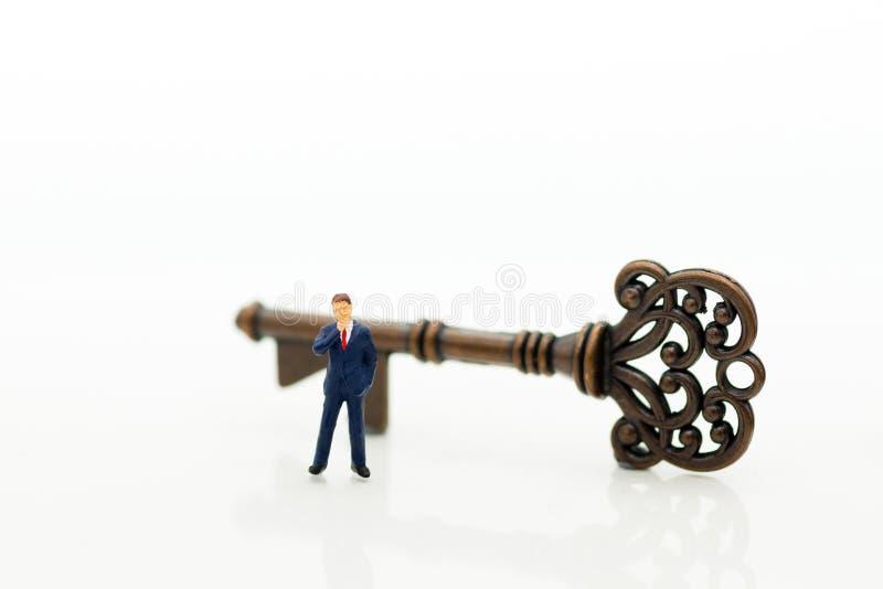 Миниатюрные люди: Стойка бизнесменов с ключами Отображайте польза для незаменимого работника, ключ к успеху, концепции дела стоковые фото