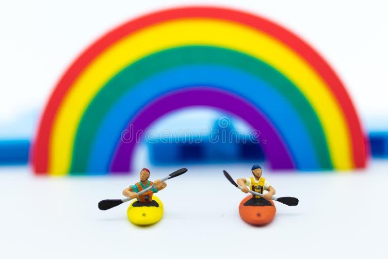 Миниатюрные люди: Туристская езда сплавляться вдоль радуги Польза изображения для концепции перемещения стоковое изображение