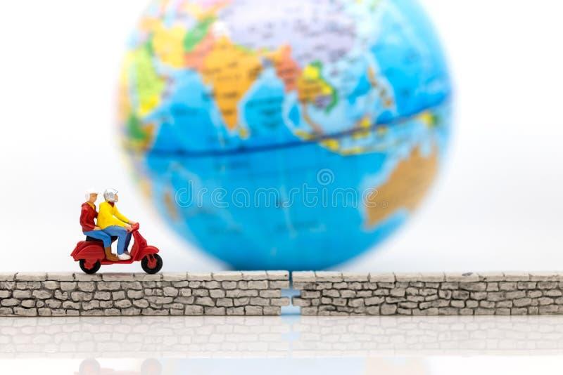 Миниатюрные люди: Туристский привод мотоцикл вдоль стены, карта мира для предпосылки Польза изображения для безопасности данных,  стоковые фотографии rf