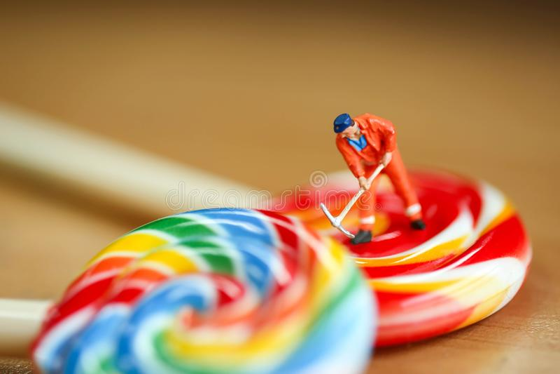 Миниатюрные люди: укомплектуйте личным составом работника с красочным конфет и loll стоковая фотография