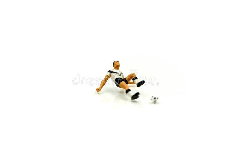 Миниатюрные люди: футболист футбола лежащ вниз раненый стоковые изображения rf