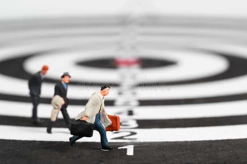 Миниатюрные люди: ход бизнесмена к идее цели dartboard разбивочной руководства конкуренции и дела стоковая фотография rf