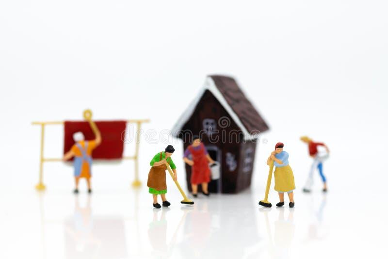Миниатюрные люди: Экономы убирают дом Отображайте польза для очищать занятия, концепцию дела стоковые фотографии rf