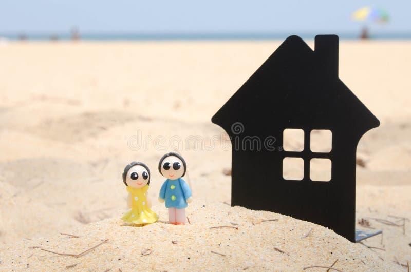 миниатюрные пары и миниатюрный дом на красивом пляже стоковые изображения
