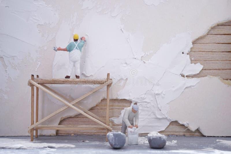 Миниатюрные работники объединяются в команду дом ремонта стоковые изображения rf