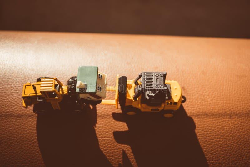 Миниатюрные трактор и грузоподъемник строительной машины использующ как жулик стоковые изображения