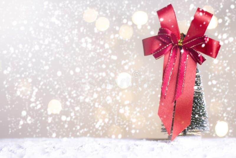 Миниатюрные cros и дерево Санты рождества на снеге над запачканной предпосылкой bokeh, изображением украшения на праздник рождест стоковая фотография