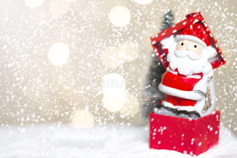 Миниатюрные cros и дерево Санты рождества на снеге над запачканной предпосылкой bokeh, изображением украшения на праздник рождест стоковые фото