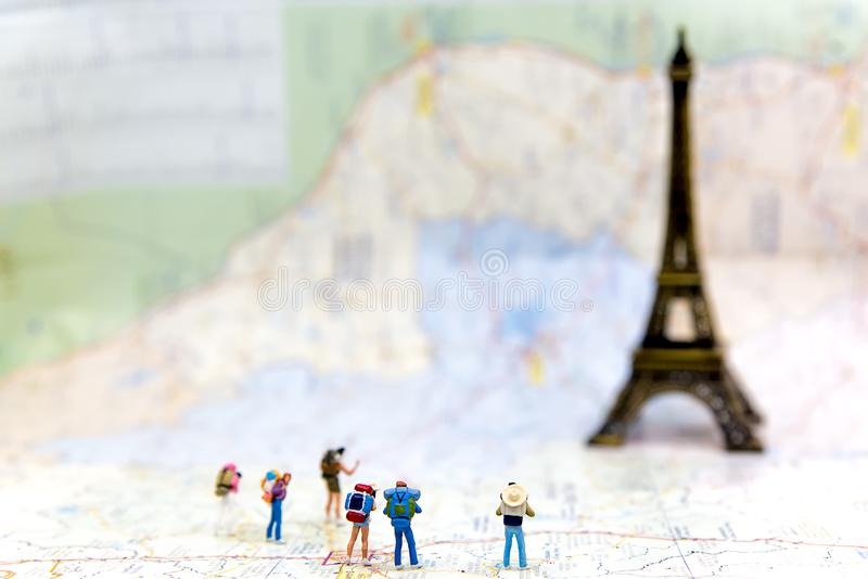 Миниатюрные hiker и путешественник группы укладывают рюкзак положение на карте пустоши для Эйфелева башни перемещения в Франции и стоковые изображения