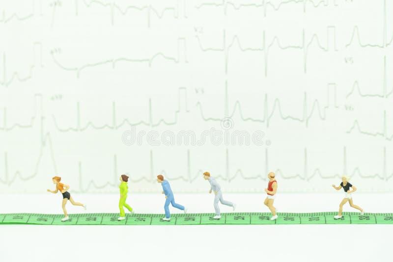 Миниатюрные joggers бегут на зеленой измеряя ленте с ба cardiogram стоковые фотографии rf
