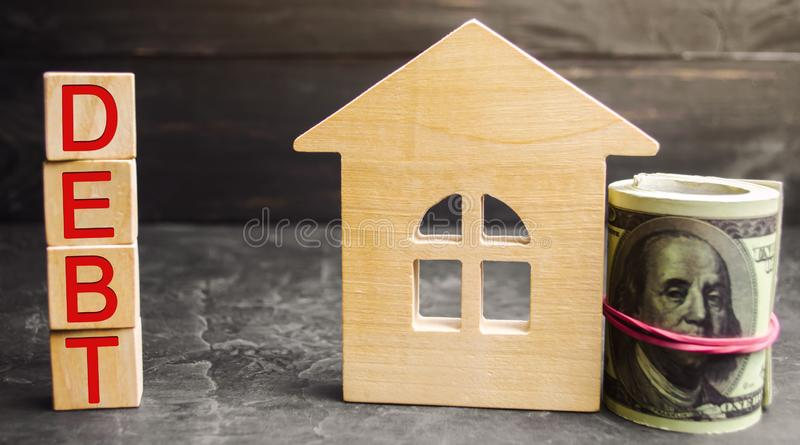 """Миниатюрный деревянный дом, доллары и надпись """"задолженность """" Недвижимость, домашние сбережения, концепция рынка займов Оплата р стоковые изображения"""