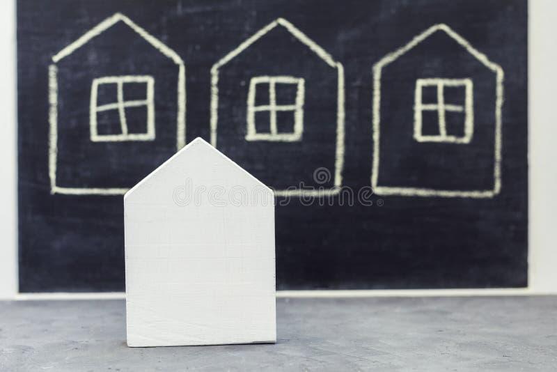 Миниатюрный деревянный дом на вычерченной предпосылке домов стоковое фото