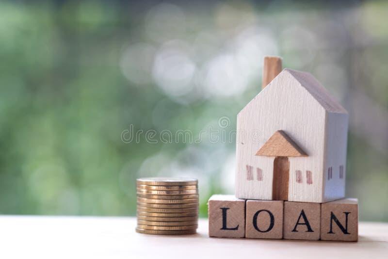 Миниатюрный деревянный дом положенный на деревянное слово блока с займом стоковое фото rf