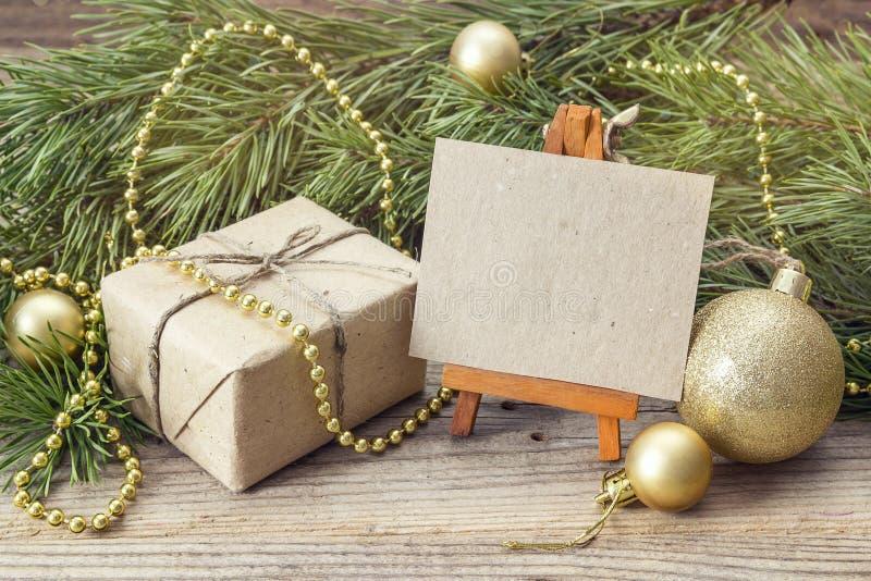 Download Миниатюрный мольберт с пустой карточкой, подарочной коробкой, ветвями сосны и Chr Стоковое Изображение - изображение насчитывающей пусто, чертеж: 81810527