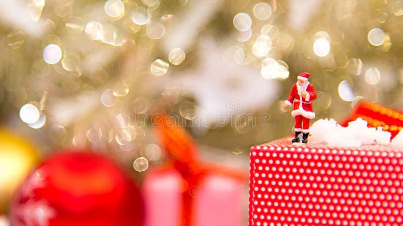 Миниатюрный Санта Клаус стоя с большими присутствующими коробками как с Рождеством Христовым стоковое изображение rf