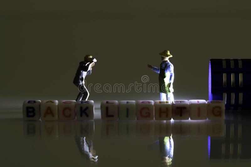 Миниатюрный фотограф фотографируя подсвеченный человек с рисбермой Свет миниатюрный голубой электрофонарь с маленькими буквами стоковая фотография