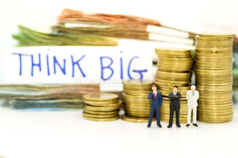Миниатюрный человек: бизнесмен с запачканным словом ДУМАЕТ БОЛЬШОЙ и много деньги Отображайте польза для дела, обязательства, сог стоковое фото