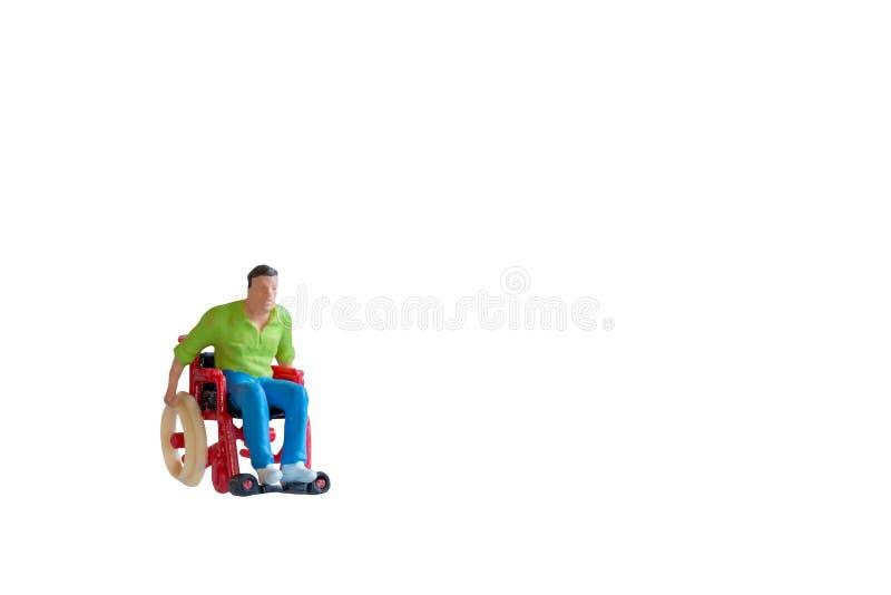 Миниатюрный человек людей в кресло-коляске изолированной с путем клиппирования стоковые фотографии rf