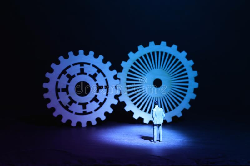 Миниатюрный человек смотря cogwheel в наборе механизма шестерней Концепция решения проблем стоковая фотография