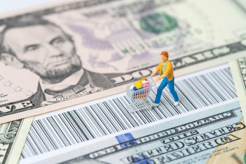 Миниатюрный figurine людей с бакалеей в вагонетке корзины идя на код штриховой маркировки с использованием денег банкнот доллара  стоковое фото