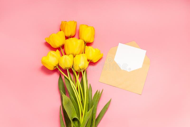 Минималистский модель-макет с красными тюльпанами, цветок карты, конверт ремесла стоковое фото