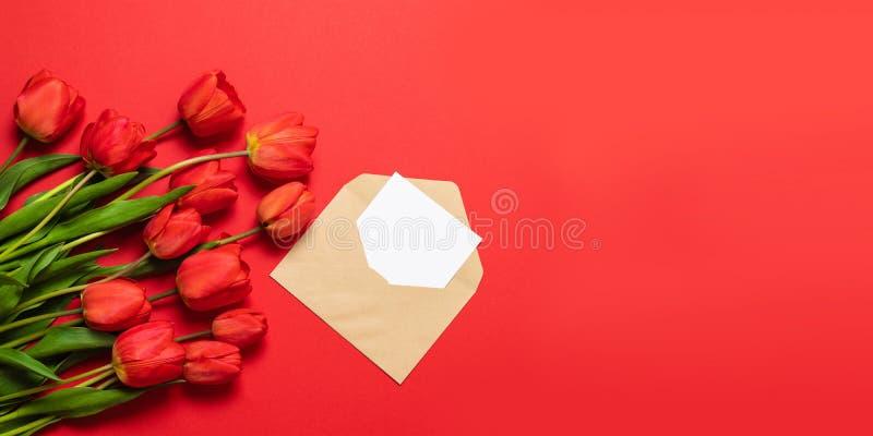 Минималистский модель-макет с красными тюльпанами, цветок карты, конверт ремесла стоковые изображения