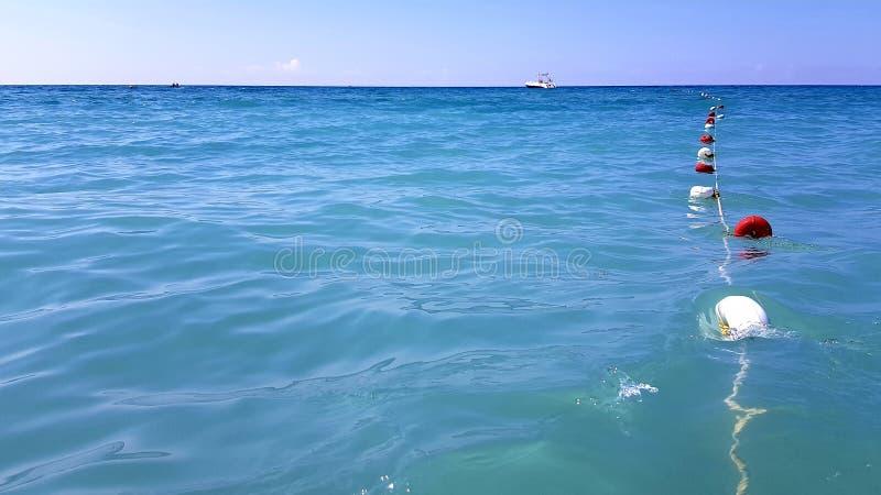 Минималистский seascape с красными и белыми томбуями на морской веревочке в морской воде штиля на море стоковые изображения rf