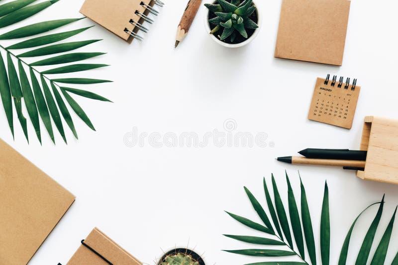 Минимальная таблица стола офиса с комплектом канцелярских принадлежностей, поставками и листьями ладони стоковые изображения