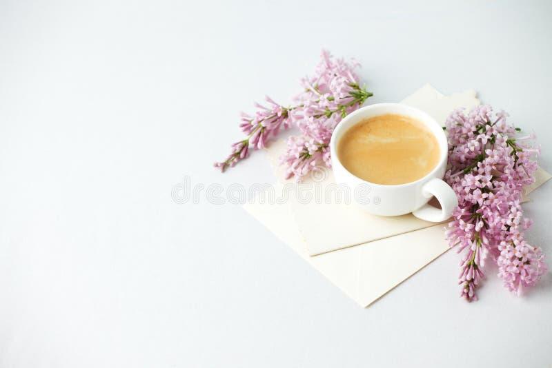 Минимальный элегантный состав с ветвями кофейной чашки и сирени, конвертом на белой предпосылке, женском завтраке утра, женщине стоковые изображения rf