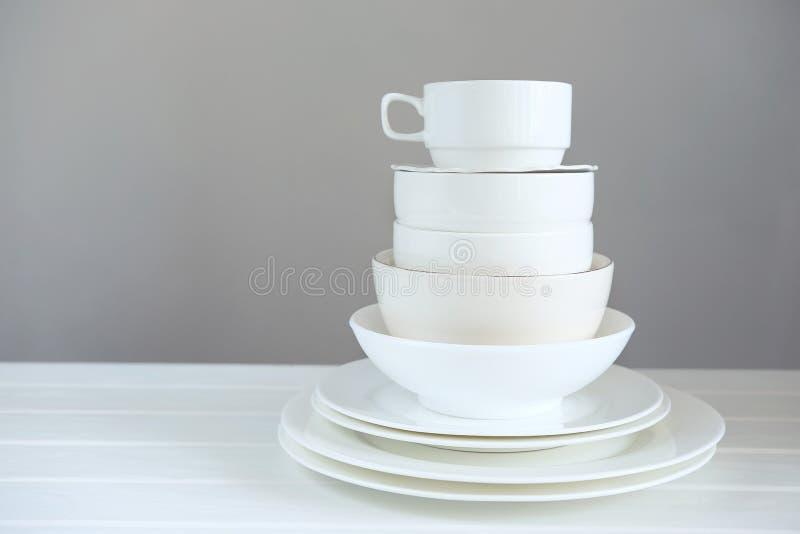 Минималистское изображение белого kitchenware фарфора сложенного вверх стоковые фото