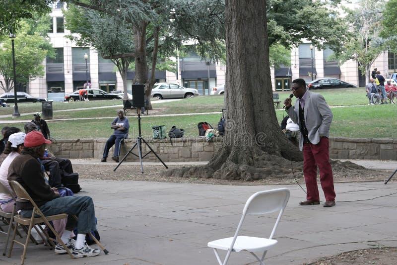 Министр церков проповедуя к бездомным людям и женщины в городе паркуют стоковые фотографии rf
