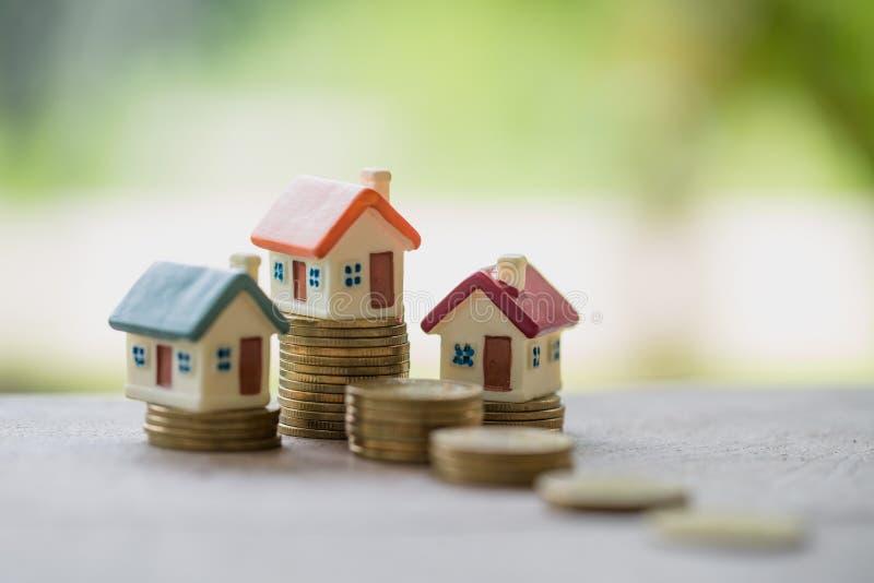 Мини дом на стоге монеток, вкладе недвижимости, сохраняет деньги стоковое изображение