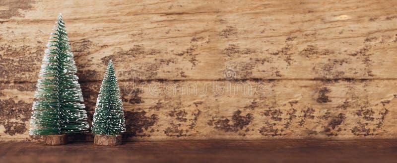 Мини древесина рождественской елки на деревенском деревянном столе и темном коричневом цвете h стоковое фото