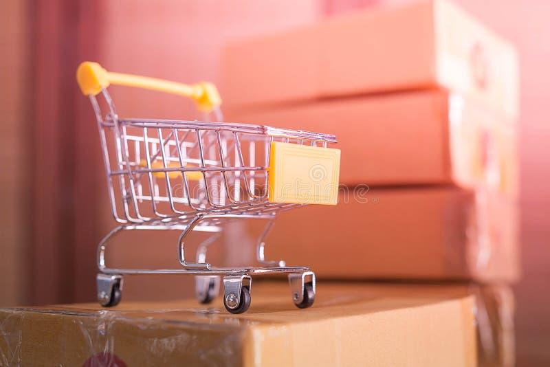 Мини желтая корзина с картонными коробками в предпосылке стоковое фото