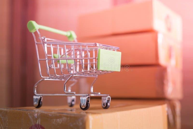 Мини зеленая корзина с картонными коробками в предпосылке стоковые фото