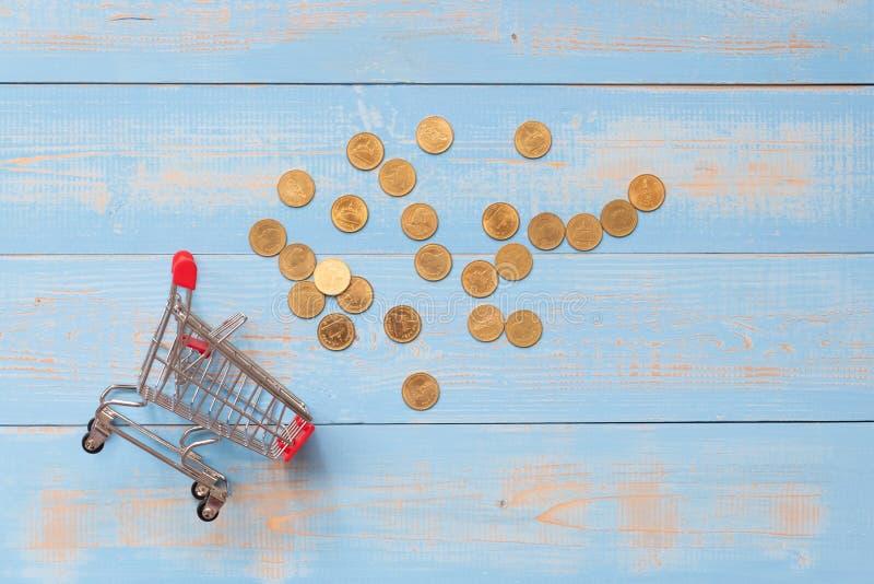 Мини магазинная тележкаа с монетками на голубом деревянном столе дело, финансы, онлайн покупки и сбережения денег на будущее стоковое фото