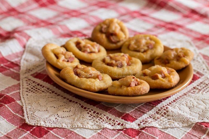 Мини пиццы в оранжевой плите на checkered скатерти стоковое фото rf