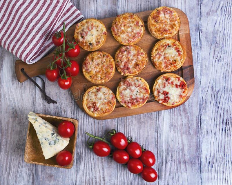 Мини пиццы на деревянном столе стоковые фотографии rf