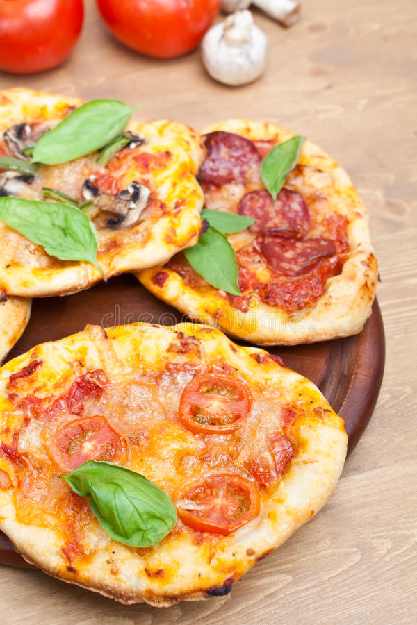 Мини пиццы на разделочной доске и ингридиентах стоковые изображения rf