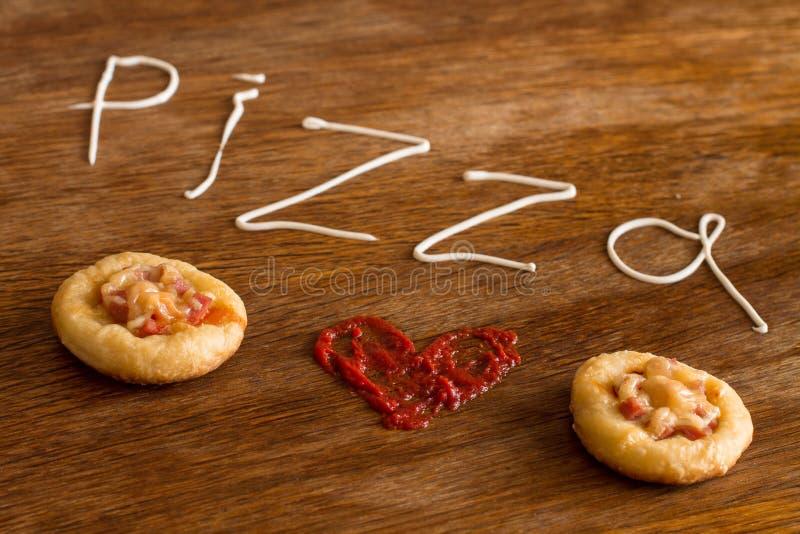 Мини пиццы с сосиской и сыром на деревянной таблице стоковое изображение
