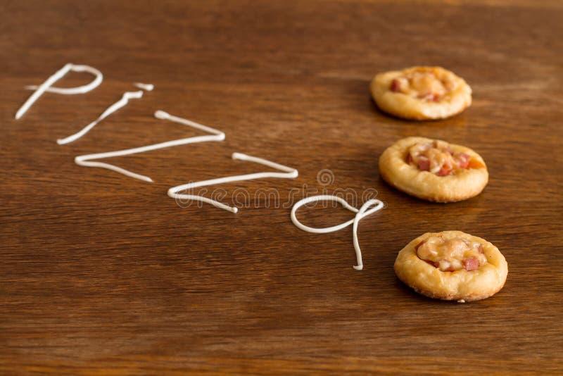 3 мини пиццы с сосиской и сыром на деревянной таблице стоковое фото rf