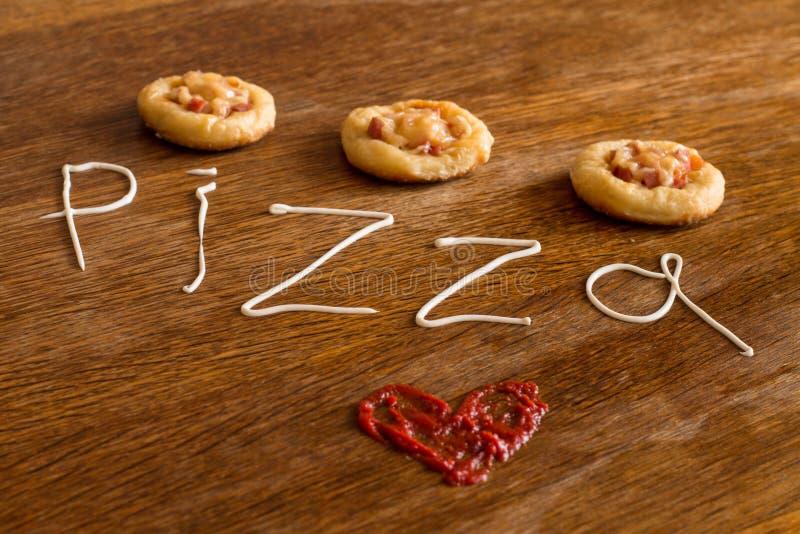 3 мини пиццы с сосиской и сыром на деревянной таблице стоковые фото