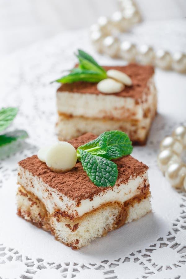 Мини тирамису тортов с белыми шоколадом, какао и конфетами на светлом конце предпосылки вверх Очень вкусный десерт и шоколадный б стоковое изображение